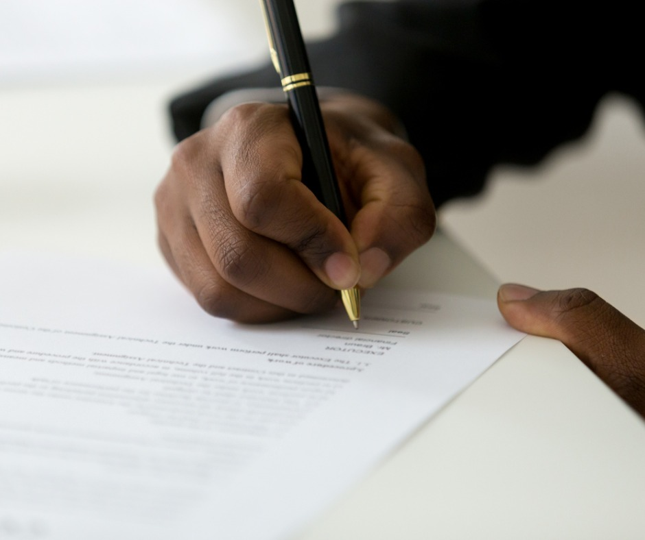 Close up of black person wearing a business suit signing legal documentation, showing their hand holding a pen and signing a contract. Image credit: fizkes (iStock). Used for faceyourfears.ca post titled Make a commitment to yourself.