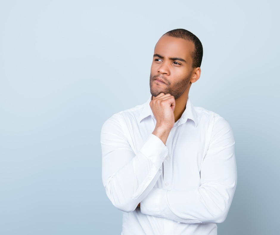 Black man wearing white dress shirt looking pensively and skeptically to his right with hand on chin, as if in deep contemplation. Image by Deagreez (iStock).