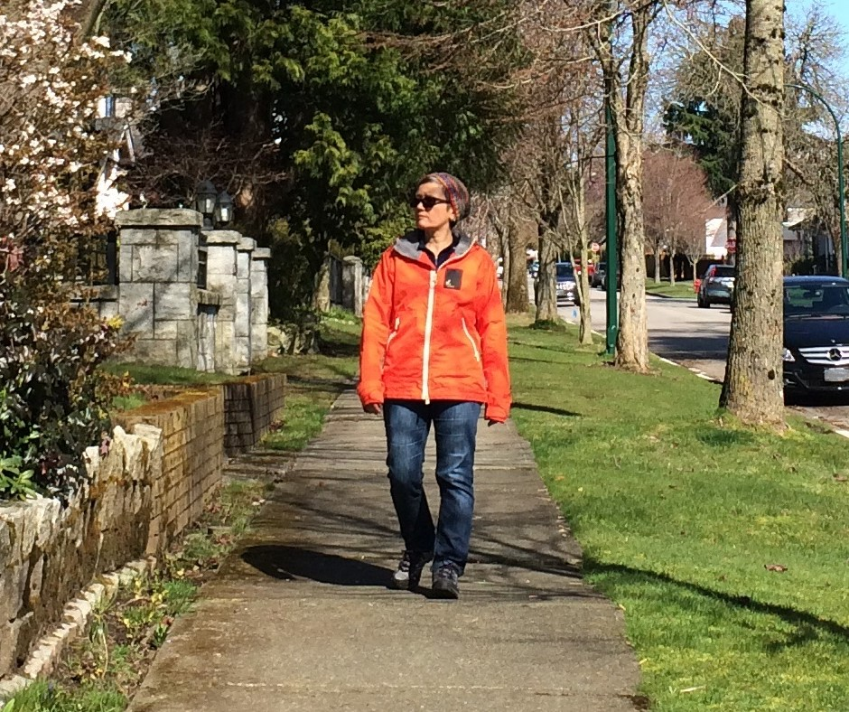 A woman (Mona Benjamintz) wearing orange jacket, jeans and a toque walking toward the viewer. Mona is walking on a sidewalk in a residential neighbourhood past houses, trees and under a blue sky on a sunny day. Image credit: Mona Benjamintz