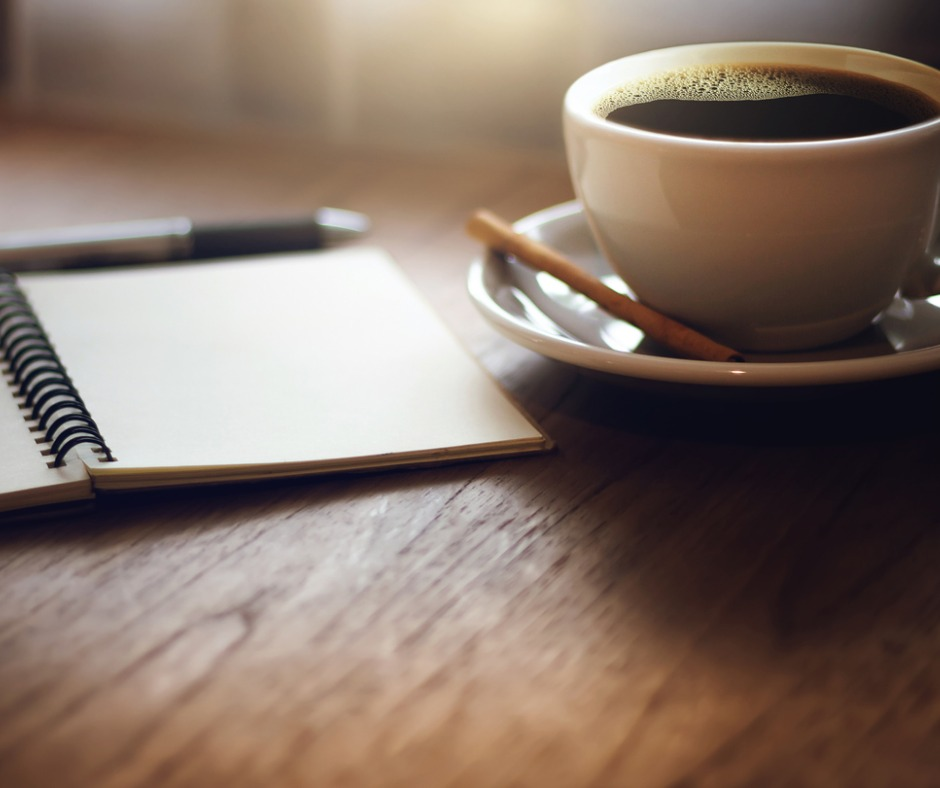 Open, coil-bound journal with pen beside it, sitting on wooden desk next to cup of coffee with a biscuit on the saucer. Table is lit from natural light from a window. Image credit: time99lek (iStock).