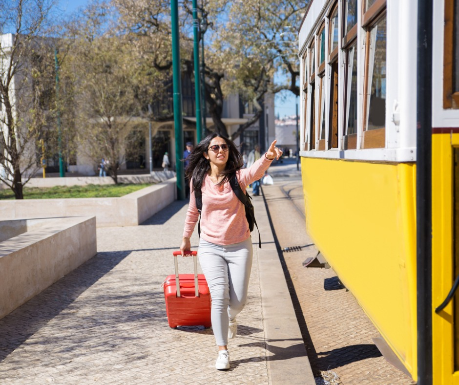 Young woman with long brown hair and sunglasses, wearing jeans, a sweatshirt and a knapsack is pulling a small rolling luggage case while waving her hand at a trolley and running to catch the trolley, outdoors, in a sunny day in a city. Image by MangoStar_Studio (iStock).