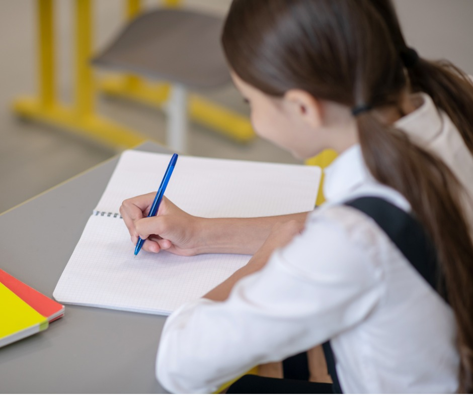 Young school girl with long brown hair worn in pig tails, wearing white blouse and dark jumper sitting at school desk, with pen in hand and a notebook on the desk. Photo views her from behind. She is diligently writing in her note book. Image by Zinkevych (iStock).