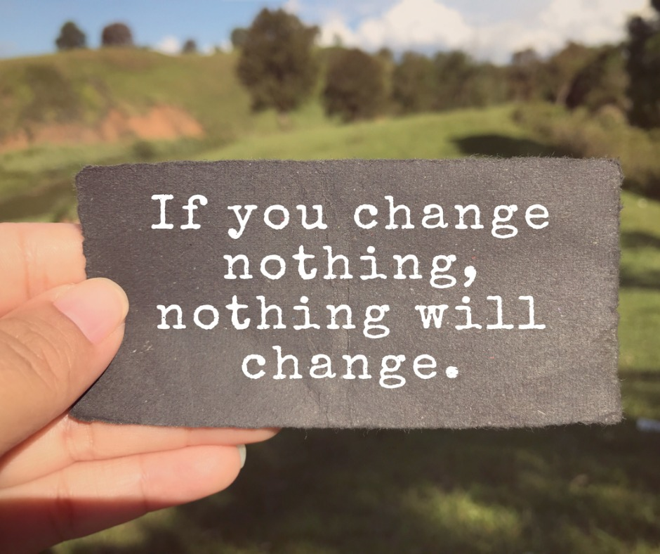 """Image used for post Fear of change - creating change: White person's fingers holding a small paper sign amidst the background of a rolling green hill with trees and a blue sky with some white clouds. Writing on the paper sign reads """"If you change nothing, nothing will change"""". Image by Coompia77 (iStock)"""