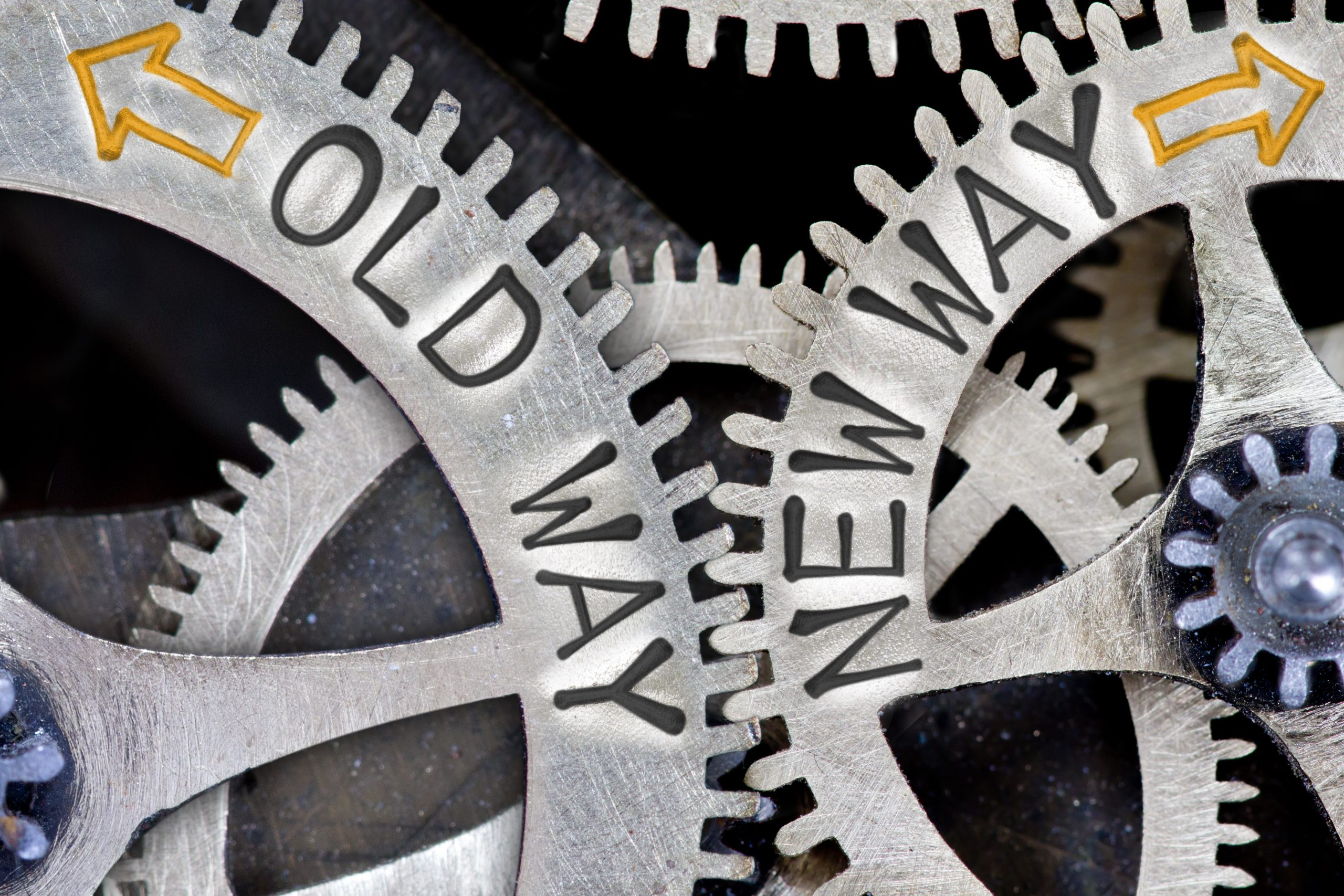 """Two metal, interlocked gear wheels, with the left wheel moving counter-clockwise and labelled """"OLD WAY"""" and the right wheel moving clockwise and labelled """"NEW WAY"""". Implies changing from the old to a new way. Image by EtiAmmos (iStock). Used for Fear of Change - Responding to Change."""